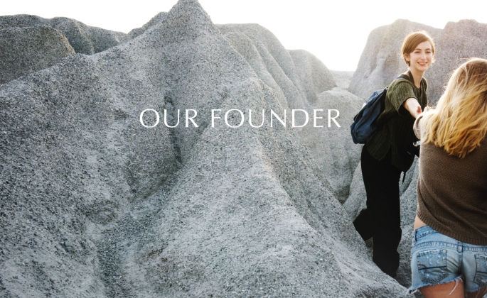 Our founder image, mountains with two women helping each other to climb them