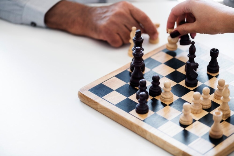 Two peoples hands moving chess pieces on a chess board. Image is to represent business strategies planning to aid success